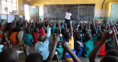 Children and teacher raise their hands. Malawi Primary School